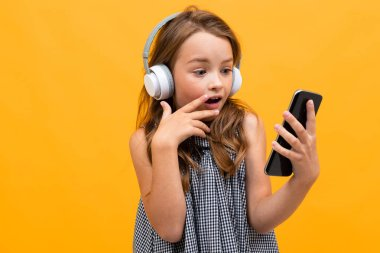 cute little girl listening to music posing against orange background