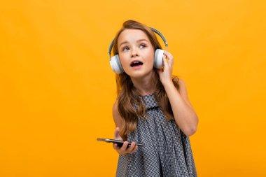 cute little girl listening to music posing against orange background