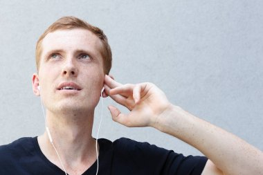 fashion, emotions and people concept - Close up portrait of a redhead beautiful manly guy. frecklessongs on smart phone with earphones, dances, gestures happily, being inspired by favourite music