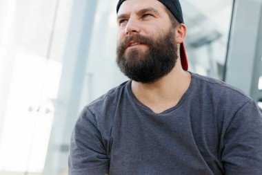 Closeup of smiling young man looking at camera. Portrait of a guy with beard who changes facial expressions. Proud and satisfied man with t-shirt looking at camera.