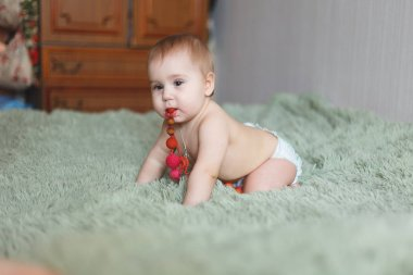 Cute adorable newborn baby of 3 moths with diapers. Hapy tiny little girl or boy looking at the camera. Dry and healthy body and skin for children concept. Baby nursery