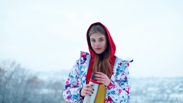 snow, winter, sport, people, beauty concept - girl pours hot tea from the thermos in the winter forest. Young woman enjoys a hot drink and smiles. ski resort
