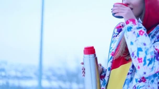 sníh, zima, sport, lidé, koncept krásy - girl nalije horký čaj z termosky v zimním lese. Mladá žena se těší, horkým nápojem a úsměvy. lyžařské středisko