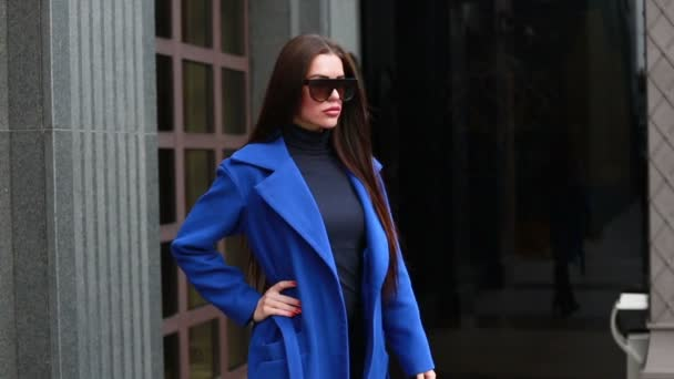 technologies, business, people beauty and lifestyle concept - Stylish female in cloak walking on the city street.