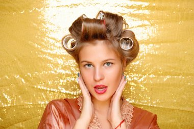 Beautiful girl in hair curlers isolated on gold