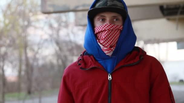 Anonymní mladý muž v balaklávě, který stojí u zdi a drží nátěr. Akt vandalismu, pouliční umění, koníček. Předměstská oblast, zábava, vzpoura, protest. Zavřít pohled
