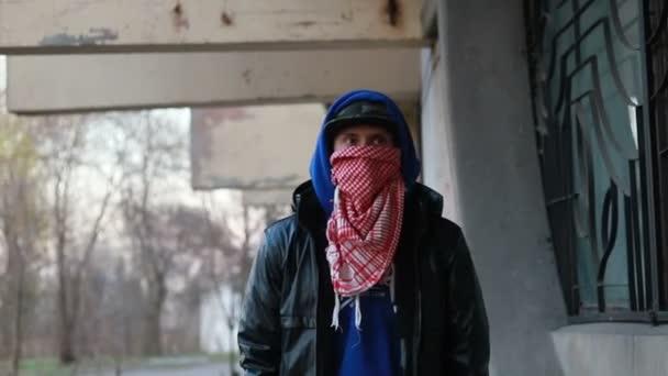 Névtelen fiatalember símaszkban áll a fal mellett, és festékszórót tart. Vandalizmus, utcai művészet, hobbi. Külvárosi terület, szórakozás, lázadás, tiltakozás. Közelkép