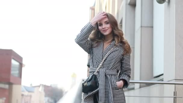 Přitažlivá dívka v kabátě na ulici ve městě svítí slunce, než se mění na kameru a úsměvy. portrét šťastný pomalý pohyb letní tvář západ slunce krásná dáma venkovní šata roztomilá