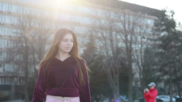 Attractive young woman walking at the sunny city streets and chatting with friends, joyful hipster girl using cellphone outdoors, sunset background
