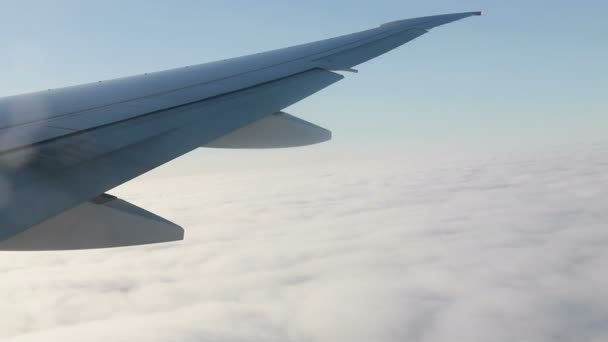 Let letadlem. Křídlo letadla letícího nad mraky se západem slunce. Pohled z okna letadla. Letadlo, letadlo. Cestuje letadlem. Video UHD 4K