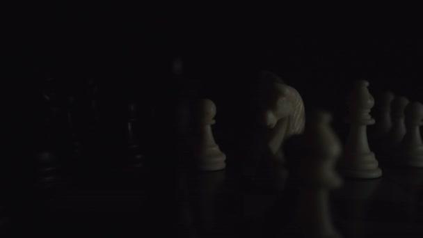 Schachfiguren auf einem Schachbrett in einem farbenfrohen Stil. Blitzlichtgewitter-Effekt. TV-Lichtkonzept, Deadline, Mode, Strategie, Start-up, Geschäft. Tiefenschärfe, weicher Fokus. Rote Kamera, 4K
