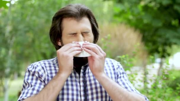 Man is standing in park. Guy is sneezing and covering nose with white napkin. After that he is mving with nose and sneezing again in napkin. Man is cleaning nose nad looking straight.