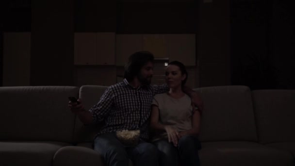 Lovely couple sits in dark and watch TV. Guy has bowl of popcorn on knees. Girl wants to get remote control. Guy doesnt want to give it but he smiles. Girl pretends she is upset but continue watch.