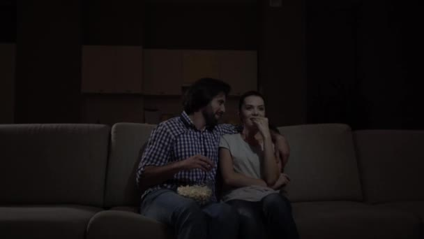 Man and woman are sittign together and watching movie. They eat popcorn and laughing. Man has bowl with popcorn on knees. They cant stop laughing. Girl points forward.