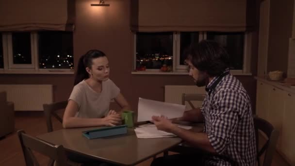 Man sits at table with woman. He takes papers and puts them back. Guy get calculator and shows it to girl. Then he throws it to table. Man is upset. Girl is too. She drinks from cup and looks at it.