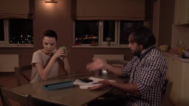 Upset man and woman sit at table. He looks at papr and start to talk. He point on himself emotionally. Then man continuous look at papers. Girl drinks from cup. She looks at man.