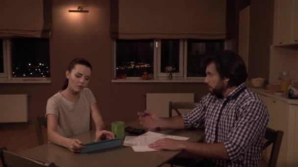 Man and woman sit at table. Girl works on tablet. Guy holds papers and talks to girl. He is upset and unhappy. Man throws papers on table and touches his hair. She looks at him.