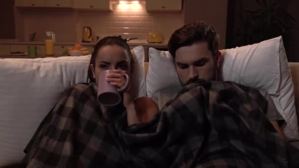 Sick couple sits together. They are covered with blanket. Girl drinks from cup. Guy get thermometer and look at it. He shows it to girl. She looks and continue drinking tea. Guy touches forehead.