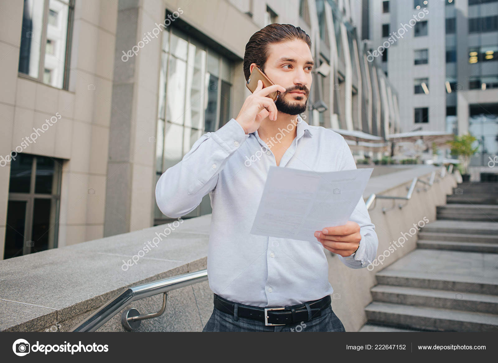 Handsome And Stylish Businessman Stands And Poses He Talks On Phone