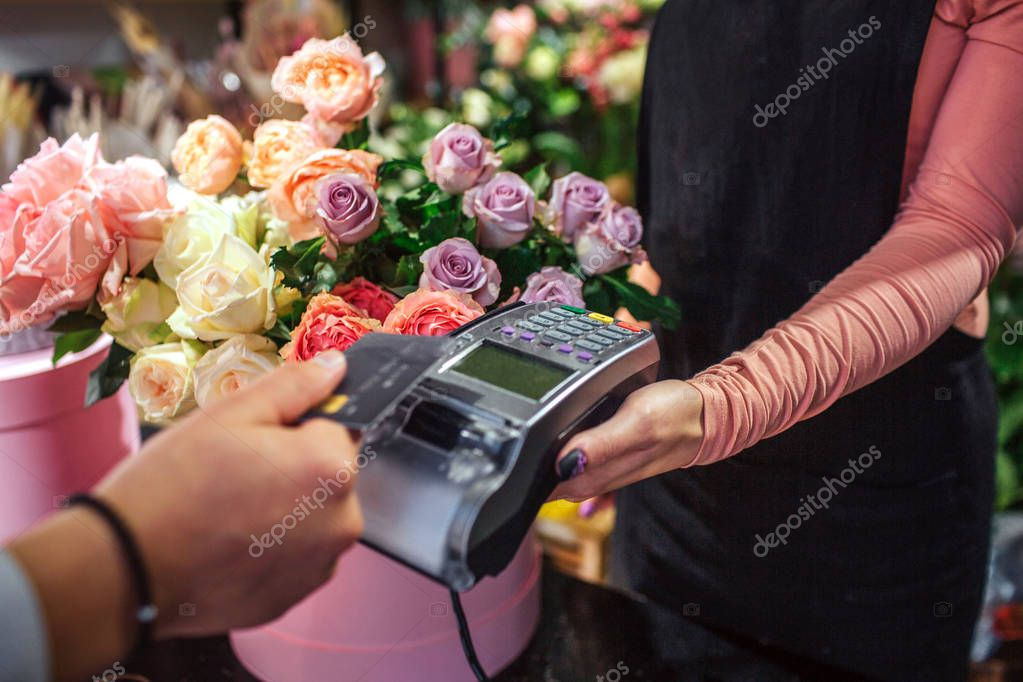 Cut view of man holding credit card above money therminal. He pays for flowers. Young female florist hold money therminal. Lots of flowers are behind her.