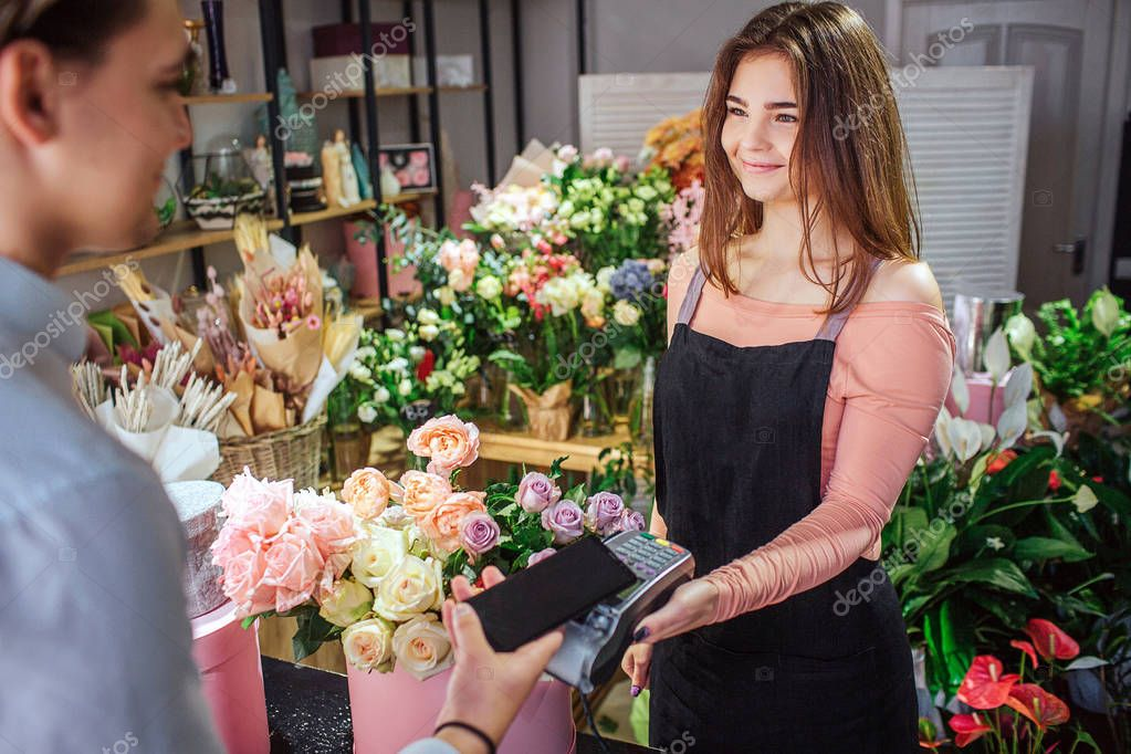 Cheerful young florist hold money therminal in hands. She looks at customer. Young businessman hold phone above therminal. He pays for flowers.