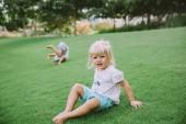 Ritratto di adorabili bambine che hanno divertimento su erba verde