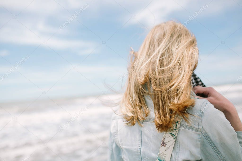 beautiful young woman looking at sea, back view
