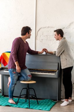 Two guys are talking hand in hand, standing in a room next to a piano
