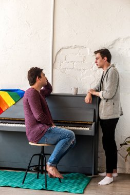 Guys taking on an intimate topic over a up of tea, in a room with a piano. Communication of guys from the LGBT community