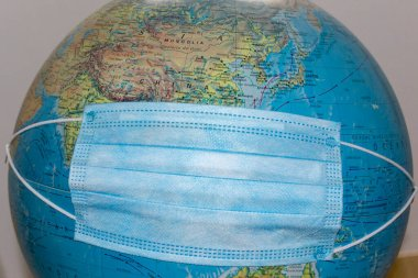 The world with a disposable medical mask due to the Coronavirus (COVID-19). Planet Earth with mask. World medical concept.