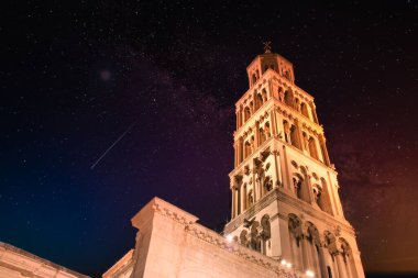 Saint Dominus belltower seen from below, long exposure, illuminated by orange lights at night, beautiful colorful night sky with purple and orange colors