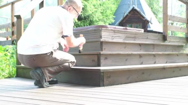 Egy fehér férfi, 45-50 éves, ecsetet tart a kezében. Festő fest egy fából készült terasz.