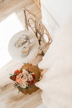 wedding shoes and wedding bouquet on the chair