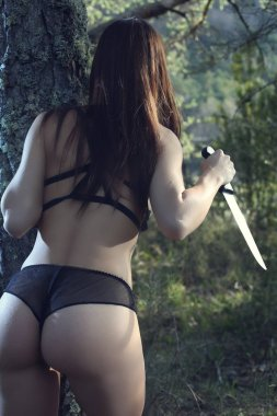 Sexy young woman in lingerie holding a knife in the forest . Horror concept