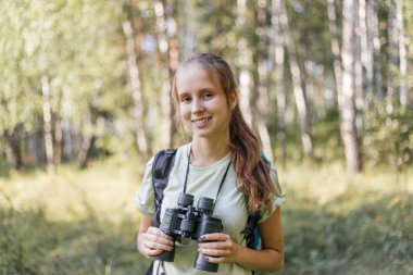 Hiker girl is looking in binoculars enjoying spectacular view