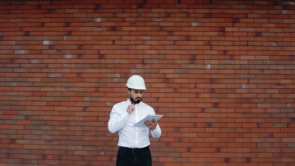 Architekt zkontroluje stavbu a projekt si zapíše. Muž s helmou je návrhář, který pracuje na projektu.