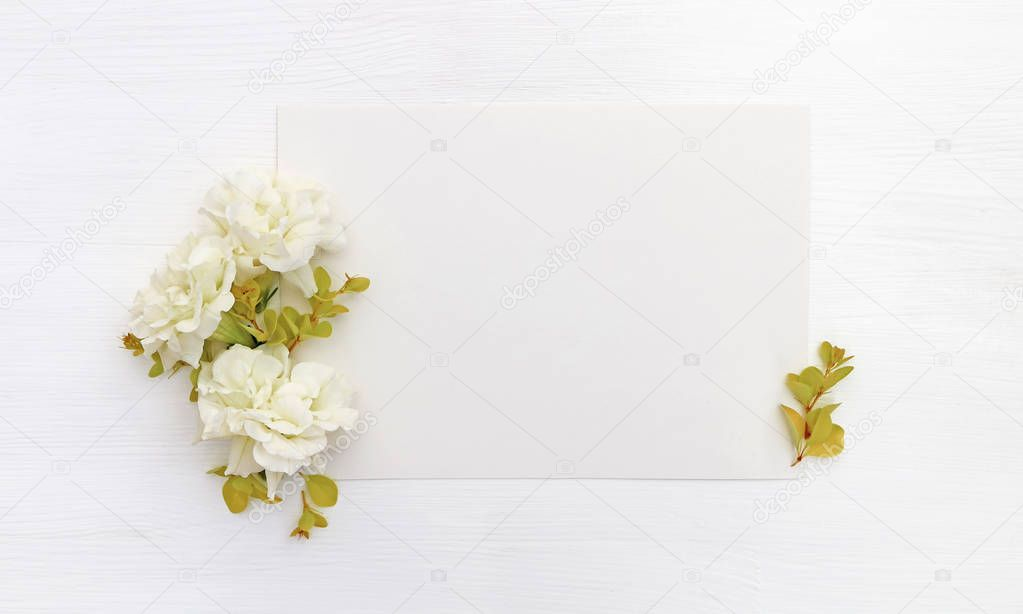 Mockup with a blank A5 paper sheet, white flowers