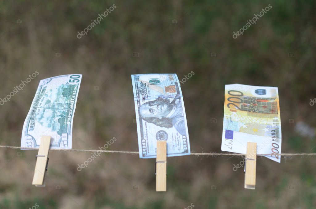 Denominations of dollars and euros on a cord on pegs