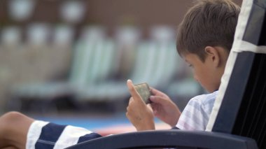 Caucasian teen boy lying on lounger operating mobile phone at swimming pool
