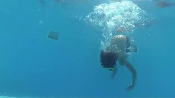 glücklicher Junge taucht in Swimmingpool und schaut in die Kamera, Unterwasseraufnahmen, Sonnenstrahlen