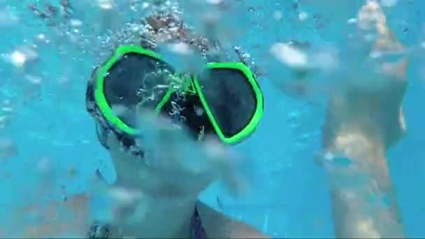 šťastná dívka v masce pod vodou v bazénu hledí do kamery, bubliny