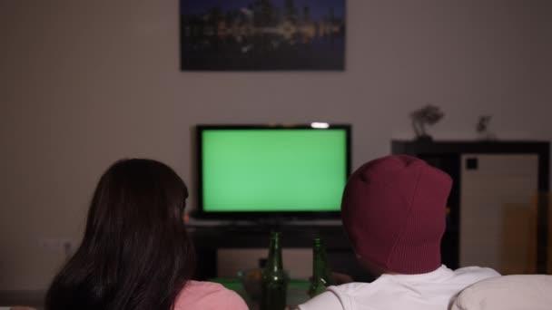 Muž se ženou relaxuje na pohovce na domácí sledování televize ve večerních a pití piva, hromakey