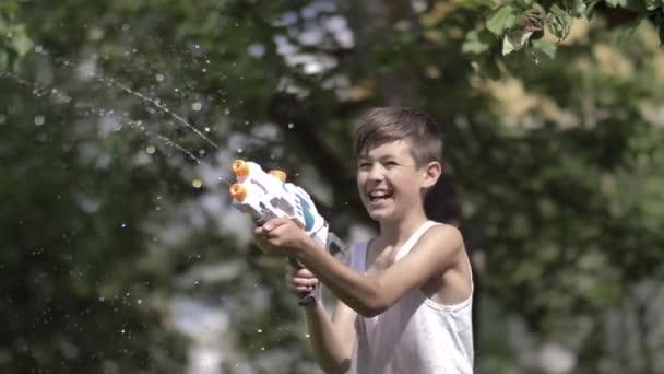 fröhlicher lustiger Junge schießt im Freien mit der Wasserpistole, hat Spaß
