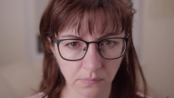 unavená smutná žena s brýlemi na kameru, pohybující se kamera