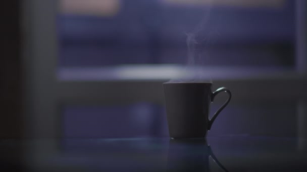 glass of hot coffee is steam on the table in the evening