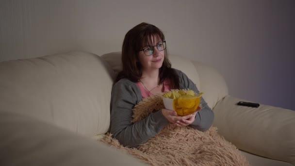boldog csinos nő szemüveges tévénézés este eszik chipset és mosolyog