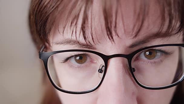 brunetka žena s brýlemi pozorně dívá na foťák zblízka, pozoruje