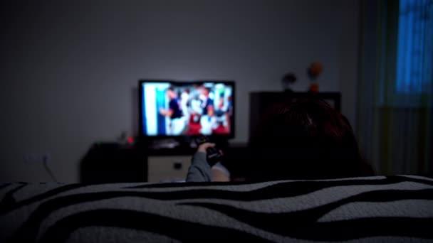 žena relaxace doma na pohovce přepínače TV kanály ve večerních hodinách, pohled zezadu