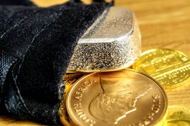 closeup of golden coins and silver brick falling out of black moneybag and laying on wooden background