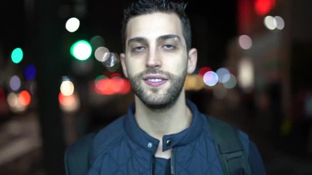 Porträt eines jungen und lustigen Typen mit Stadtnacht im Hintergrund
